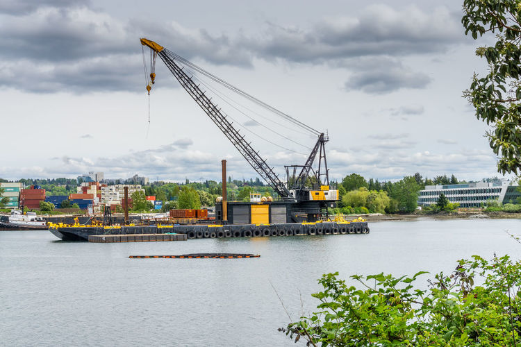 Crane at commercial dock by river against sky