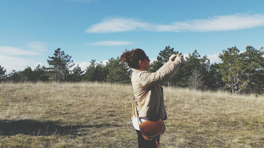 Side view of woman photographing while standing against blue sky