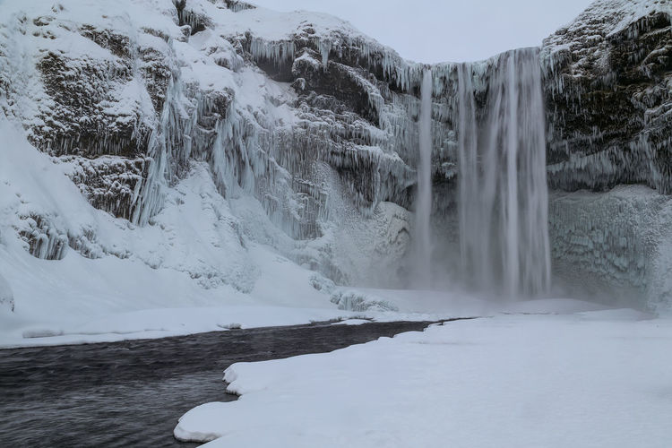 Scenic view of waterfall against snowcapped mountains during winter
