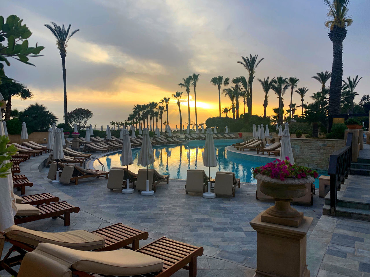 sky, water, chair, tropical climate, sunset, tree, nature, seat, plant, cloud - sky, palm tree, swimming pool, table, pool, no people, beauty in nature, tourist resort, tranquility, sea, outdoors, setting