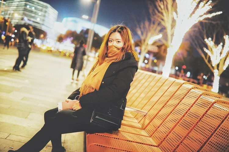 Beautiful Woman Lifestyles One Person Young Adult Portrait Looking At Camera Smiling Night Outdoors Real People Young Women Beauty Happiness City Beautiful People Sitting Warm Clothing Adult People Close-up