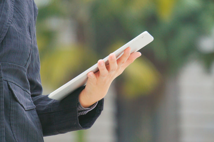 Midsection of person holding digital tablet outdoors