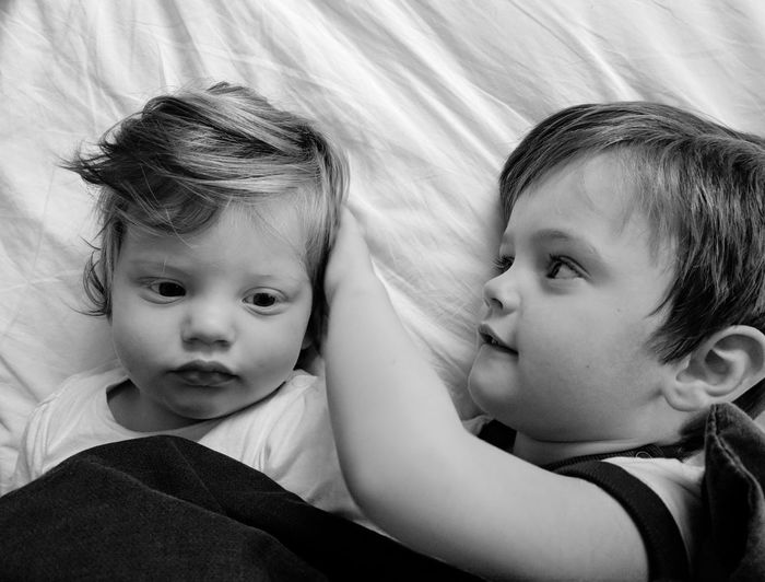 High Angle View Of Siblings Lying On Bed At Home