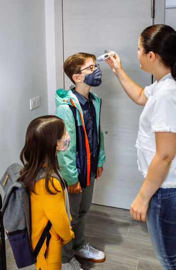 Woman checking temperature of kids indoors