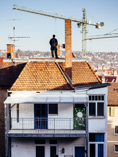 Rear view of man standing on building roof