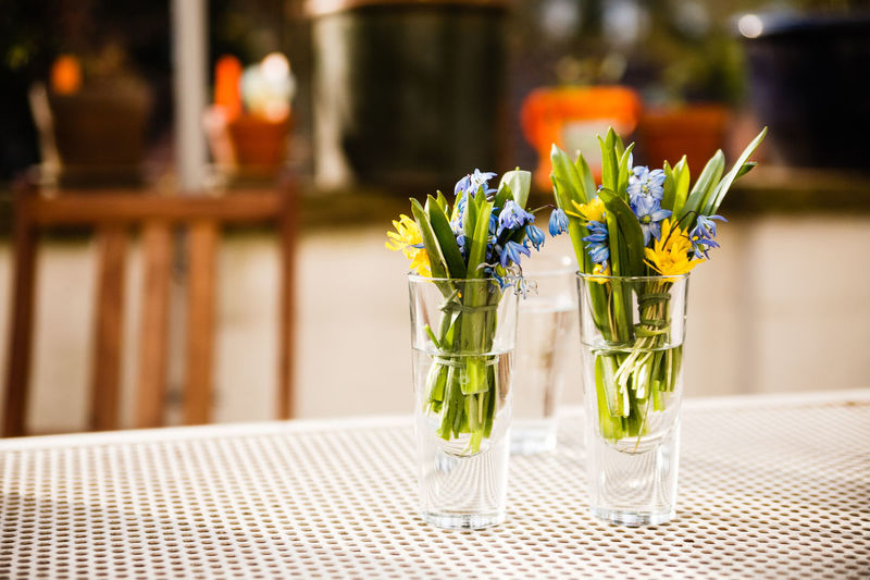 Flowers In Glasses On Table At Sidewalk Cafe