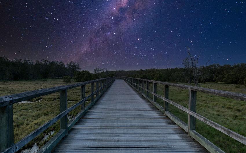 Footbridge against sky at night