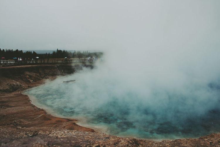Smoke on hot spring against sky