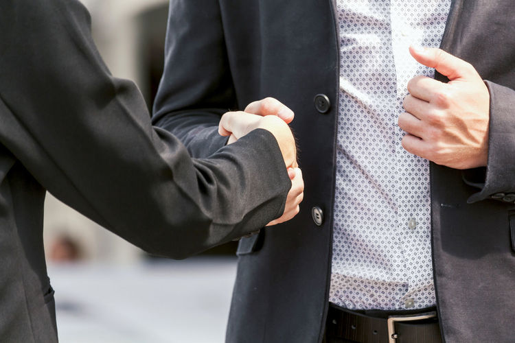 Midsection of woman with colleague handshaking on footpath