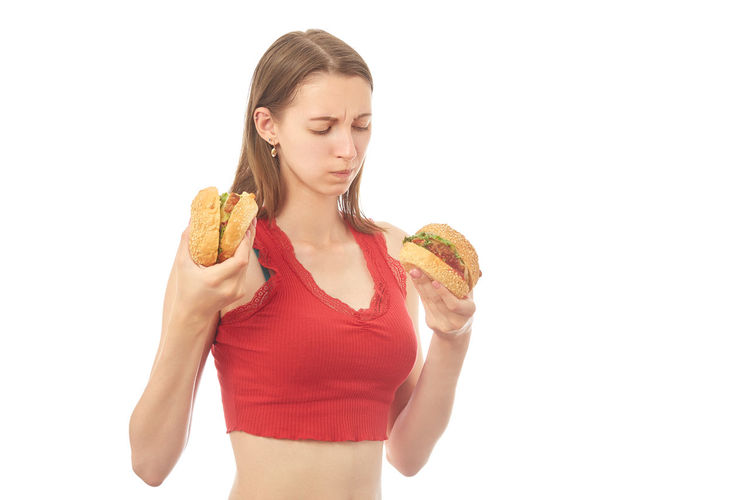 Young woman eating food against white background
