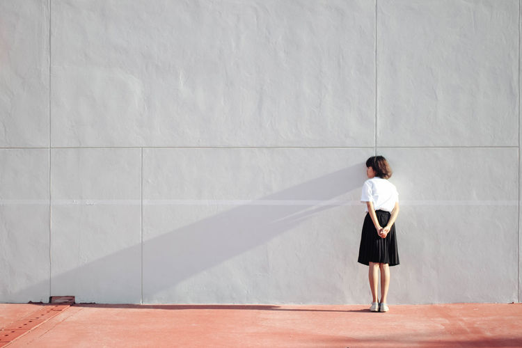 Rear view of young woman standing against wall