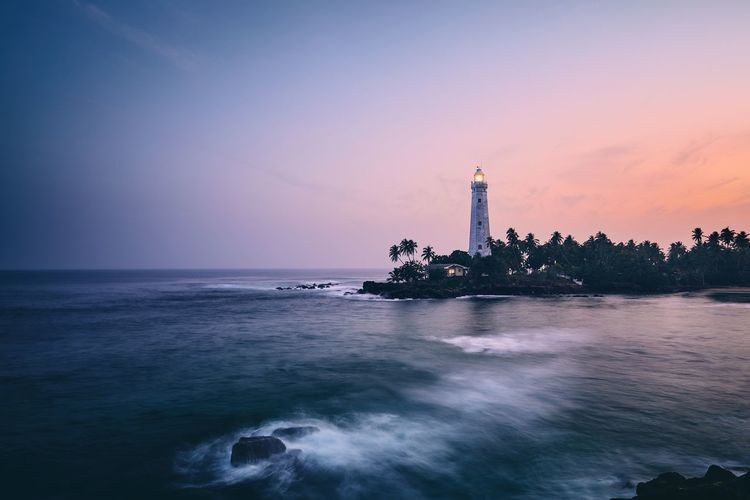 Illuminated lighthouse in the middle of palm trees. South coast of Sri Lanka at sunset. Lighthouse Sunset Coastline Sri Lanka Sea Seascape Wave Architecture Building Exterior Guidance Direction Light Building Moody Sky Sky Water Nature Travel Destinations Scenics - Nature Beauty In Nature Horizon Over Water Travel Palm Tree Landscape Landmark