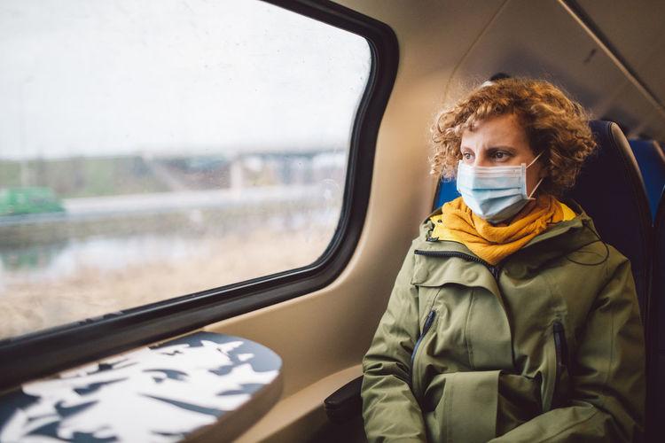 Portrait of mid adult woman seen through train window