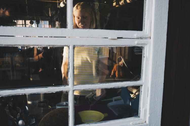 Girl looking through glass window