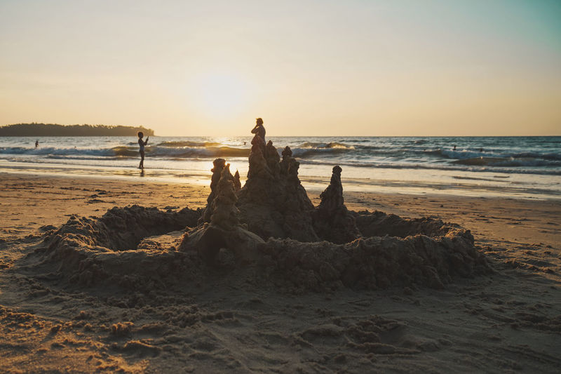 Scenic view of sandcastle at sea against sky during sunset