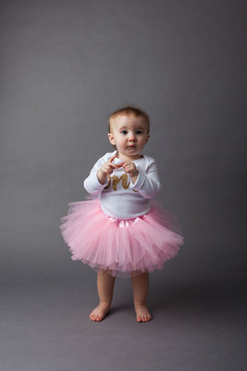 Baby Girl Wearing Dress Standing Against Gray Background