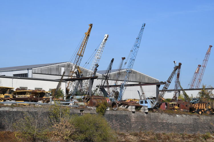 Cranes at construction site against clear blue sky