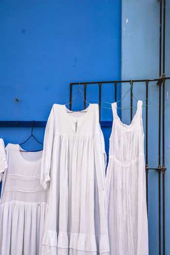 White dresses hanging on gate against blue wall at market