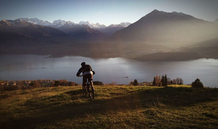 Man cycling on mountain by lake at sigriswil
