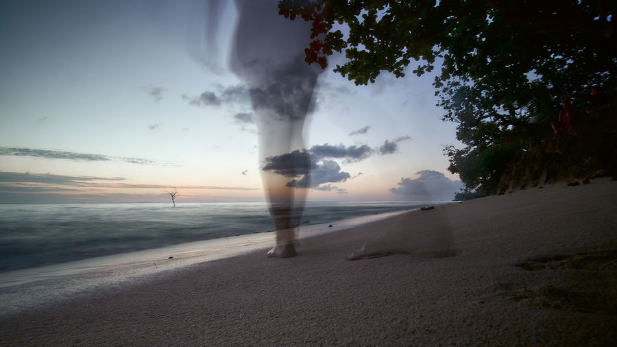 Blurred motion of man on beach against sky