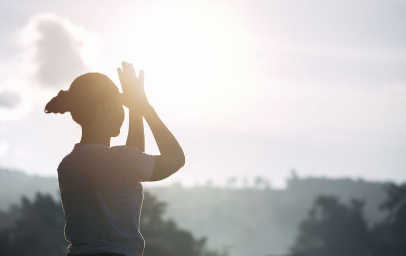 Side view of silhouette woman standing against sky