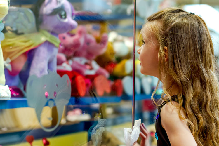 Girl looking at stuffed toy in store through glass window