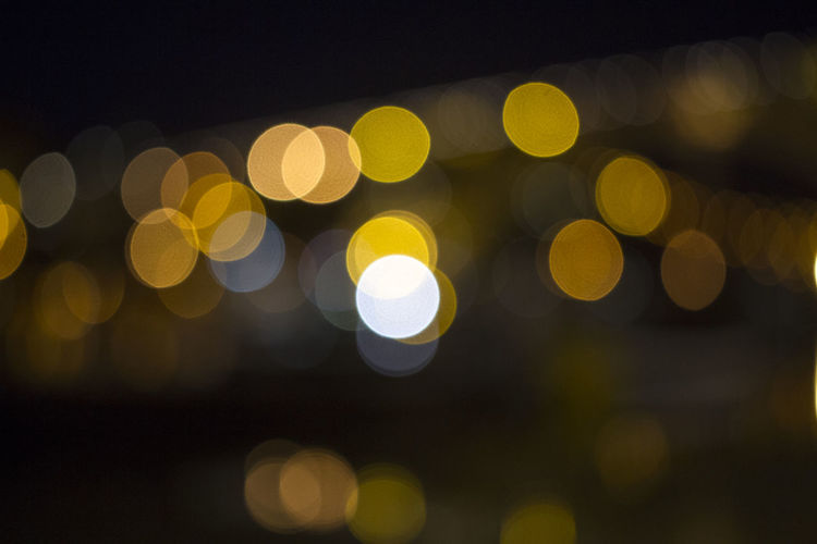 Defocused image of illuminated yellow lights at night