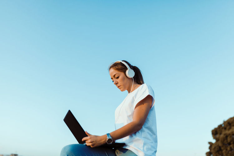 Low angle view of young woman using laptop against clear sky