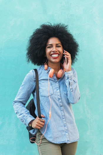 Beautiful afro american woman using her mobile in the concept. Adult African Afro American Beautiful Casual Copy Space Hair Headphones Lifestyle Woman Attractive Beautiful Black Communication Denim Ethnic Mobile Outdoors People person Portrait Smart Phone Street Urban