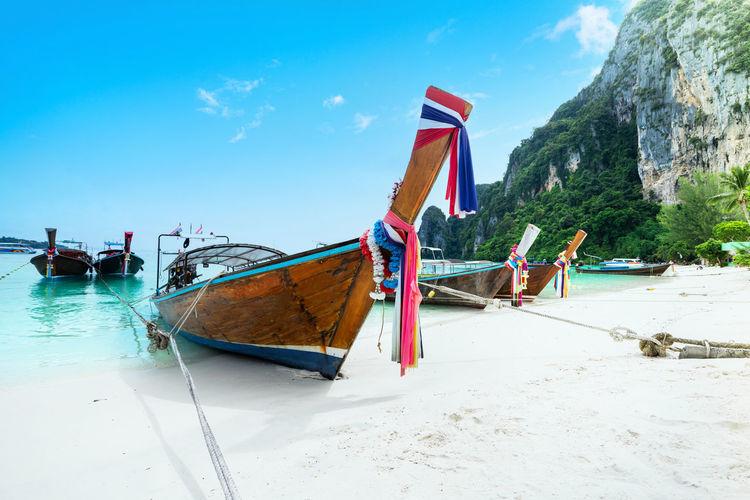 Boats moored on beach against sky
