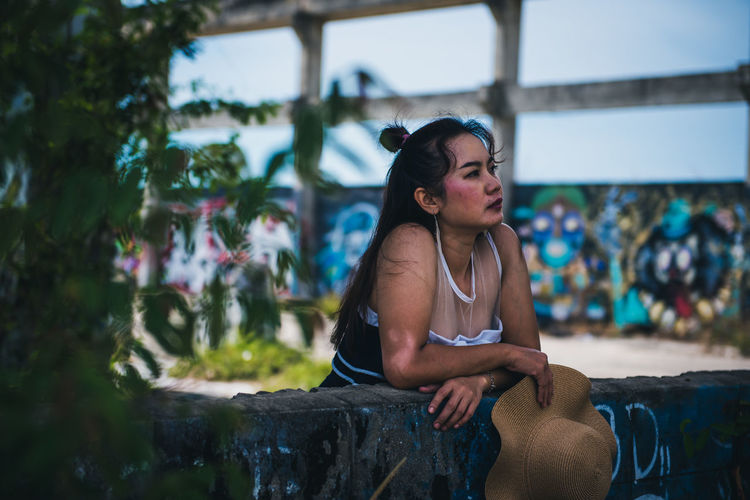 Side view of young woman sitting outdoors