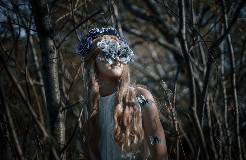Woman wearing mask standing amidst plants