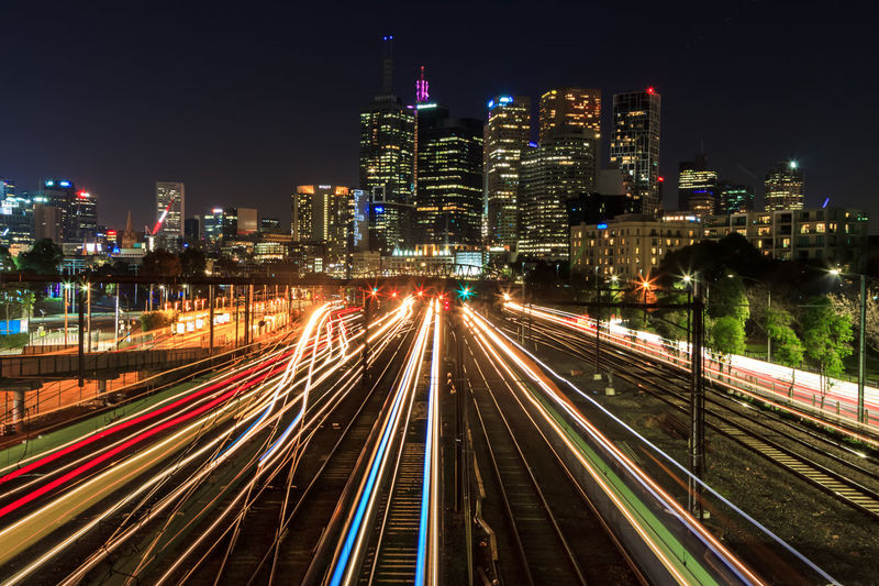 High angle view of train light trails amidst buildings in city at night