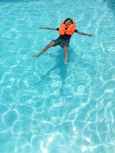 High angle view of young boy floating on water with swimming aid
