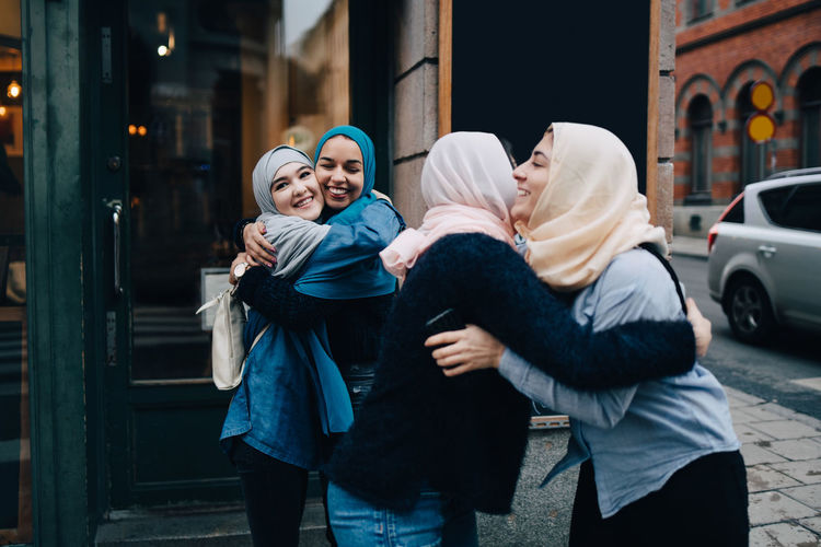 Smiling multi-ethnic female friends greeting on sidewalk in city