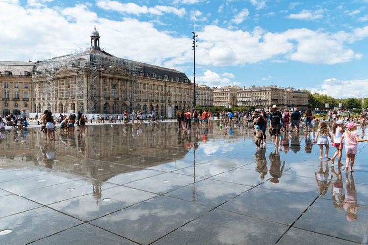 People on wet street against cloudy sky in city