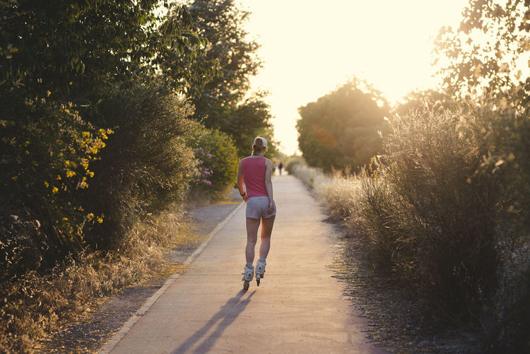 Young woman having fun while roller skating outdoors during female wearing a pale pink cap, headphones and sports clothes doing exercise. Casual Clothing Day Direction Footpath Full Length Leisure Activity Lifestyles Nature One Person Outdoors Plant Real People Rear View Road Shorts Sunlight The Way Forward Transportation Tree Walking Women