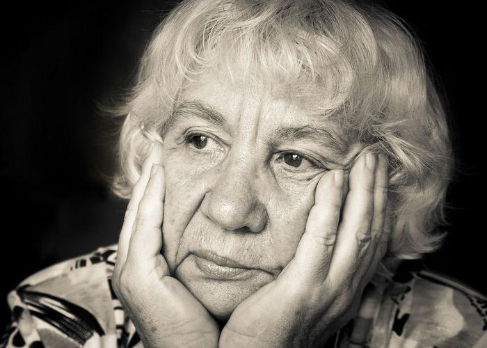 Sad senior woman against black background