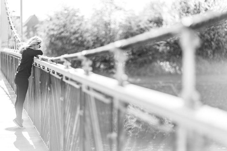 Side view of woman standing on footbridge