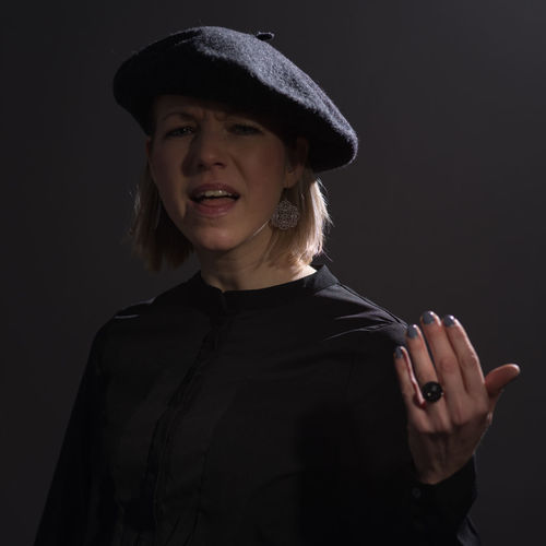Portrait of mid adult woman gesturing against gray background