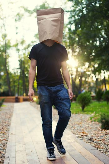 Man Wearing Paper On Head While Walking On Footpath