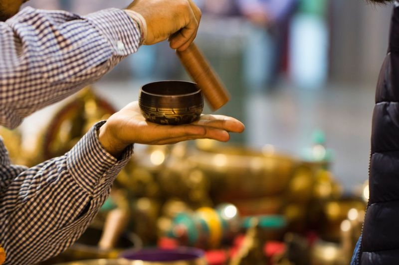 Cropped image of man playing tibetan singing bowl