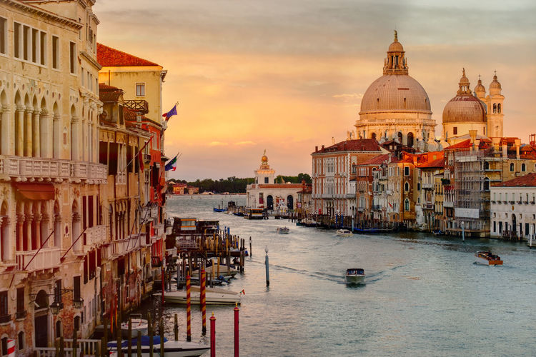 Santa maria della salute by grand canal and building against cloudy sky during sunset