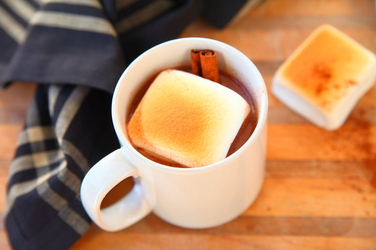 Hot chocolate with giant toasted marshmallow Cup Mug Refreshment Table Hot Drink Close-up Wood - Material Indoors  Marshmallows Hot Cocoa  Hot Chocolate Dishcloth Cinnamin Stick Spice Overhead Natural Light Homemade Drink Winter Room For Text Cutting Board Copy Space Studio Shot Delicious