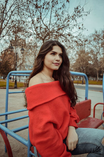 Beautiful young woman sitting on outdoor play equipment at playground