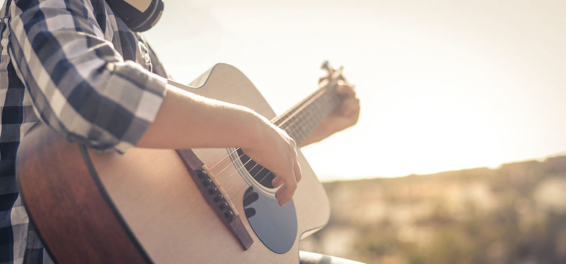 Midsection of boy playing guitar outdoors