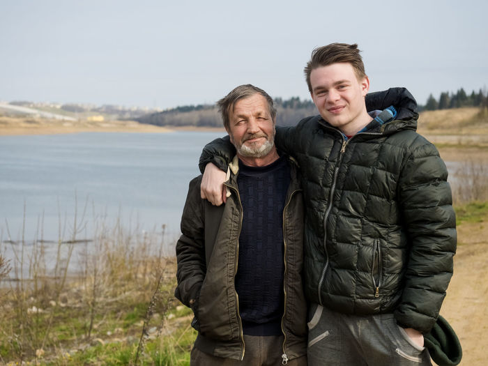 Portrait of smiling son and father standing against lake