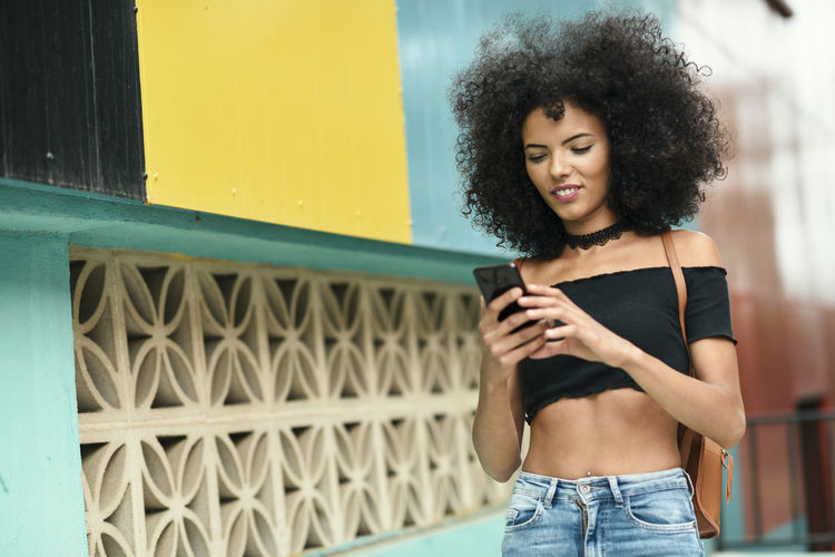 Smiling Young Woman With Curly Hair Using Mobile Phone While Standing By Building