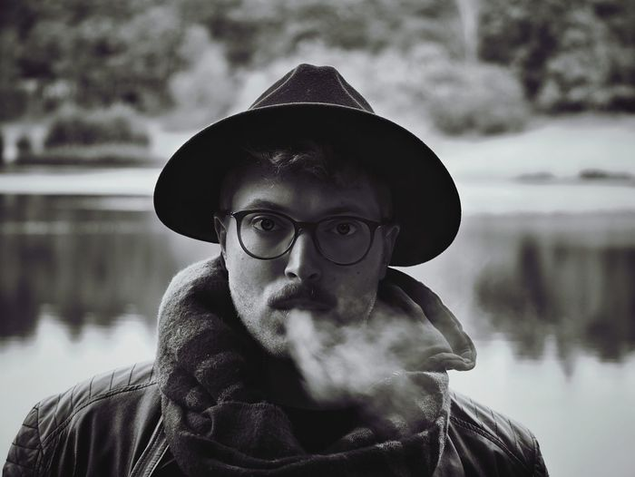 Portrait Of Man Exhaling Smoke Against Lake