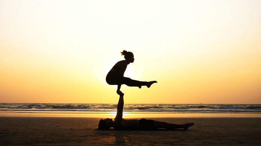 Man and woman doing yoga at beach
